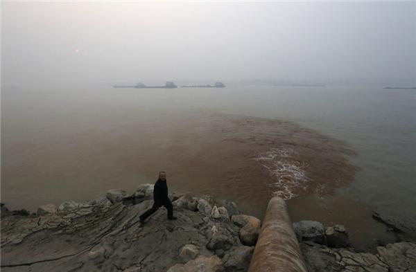 Một người đàn ông bước qua đường ống cống xả nước thải thẳng ra sông Dương Tử.