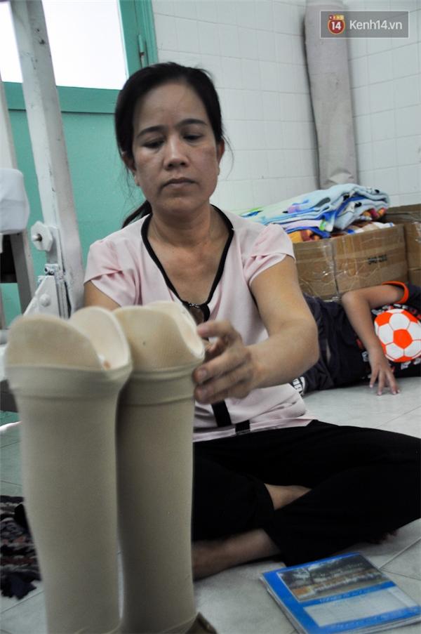Sau khi dùng cơm xong, người mẹ lại chuẩn bị sách vở và chỉnh trang lại đôi chân giả cho con để chuẩn bị đi học.