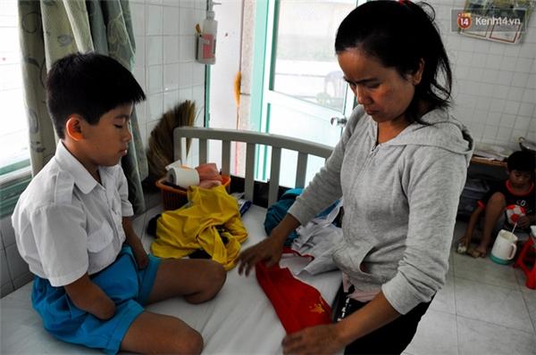 """Khi mặc quần áo đi học thì bé phải nhờ sự trợ giúp của mẹ, còn những việc còn lại thì bé Lâm tự làm lấy. """"Những việc nào cháu làm được thì cố gắng làm không muốn để mẹ vất vả. Cháu không muốn cắt chân, cắt tay nữa đâu đau lắm"""", bé Lâm thường hay chia sẻ nỗi sợ hãi với mẹ."""
