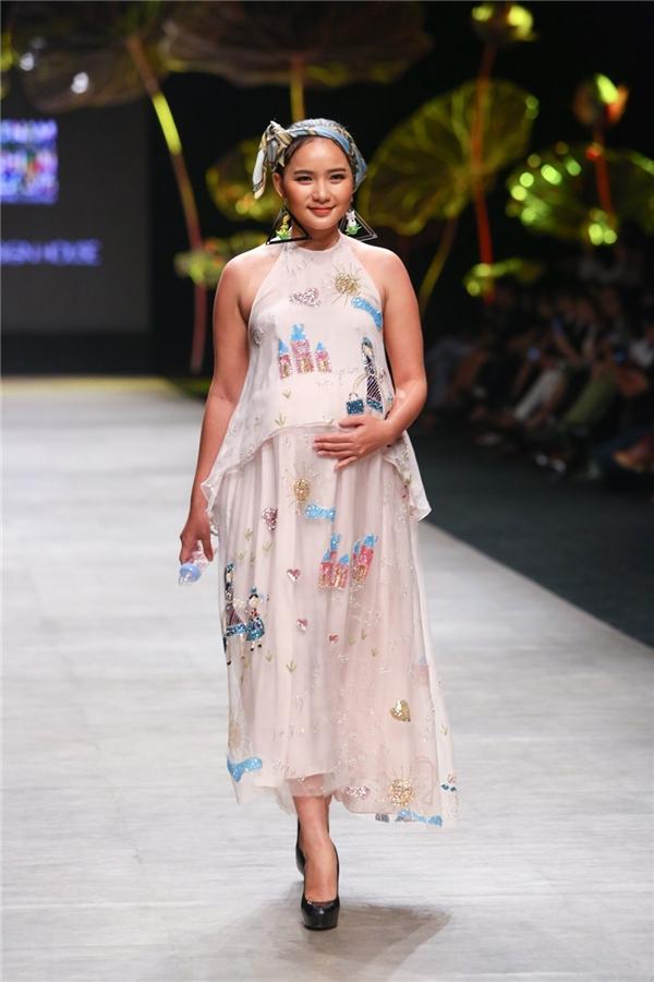 """Ngay phần mở màn, khán giả phải """"ồ"""" lên khi Phan Như Thảo xuất hiện với phần bụng khá to ở tháng thứ 5 của thai kì. Tuy nhiên, nữ người mẫu vẫn sải bước chuyên nghiệp, quyến rũ, đầy thu hút."""