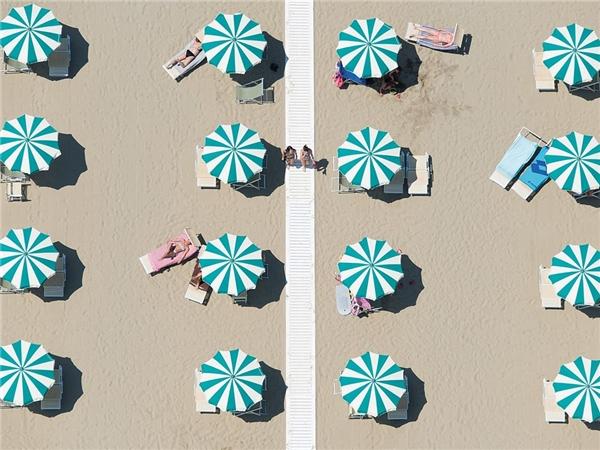 Hàng ô xanh trắng trên bãi biển Rimini, Italy.