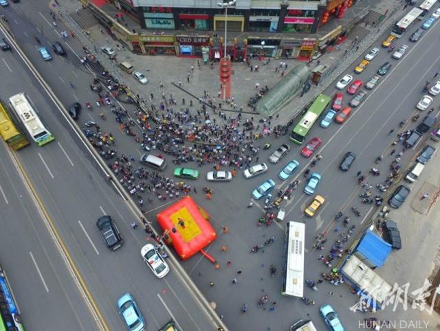 Người thanh niên leo lên cột đèn giao thông với ý định tự tử thu hút sự chú ý của rất nhiều người. (Ảnh: Hunan Daily)
