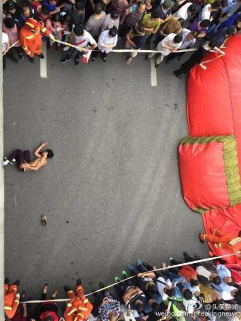 """Bỗng đâu xuất hiện vài người đàn ông """"quá tốt bụng"""" nhiệt tình giúp đỡ khiến người thanh niên kia... bực bội và mất tập trung nên bị ngã xuống đất... bên cạnh tấm nệm cứu hộ và tính mạng rất nguy kịch. (Ảnh: Hunan Daily, weibo.com)"""