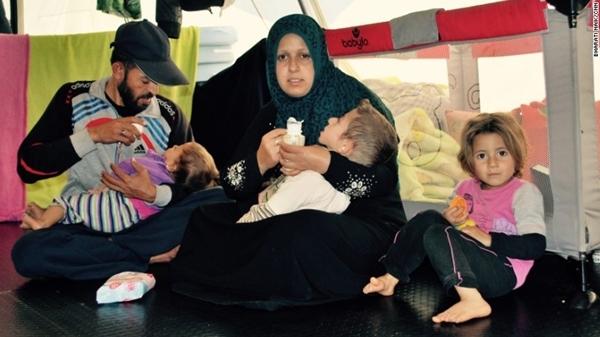 Alyaman nằm trong lòng mẹ, xung quanh là gia đình cậu bé.