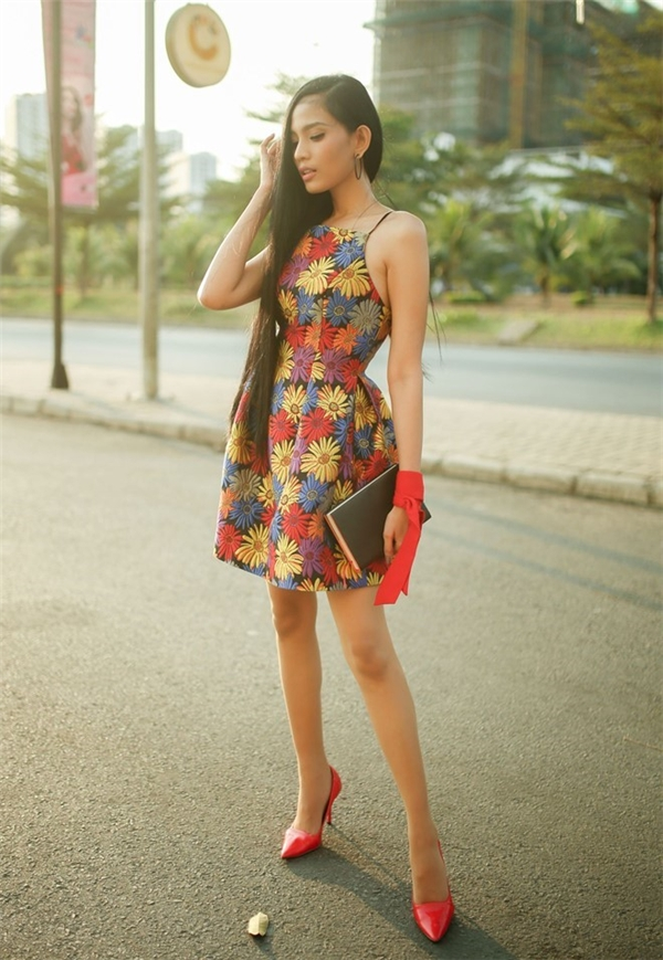 Trương Thị May mang đến khu vườn hoa nhiệt đới đầy màu sắc trên dáng váy xòe cổ yếm. Phụ kiện đi kèm được cô kết hợp đồng điệu với màu sắc của họa tiết.