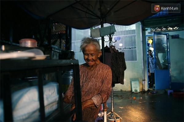 """Mỗi khi trời mưa, không đi bán được, cụ lại ngồi trước nhà như thế này, ông Minh liên tục bảo mẹ vào nhà nhưng cụ đều đáp: """"Vô đó chật chội vướng víu tụi con chứ được gì đâu!"""""""