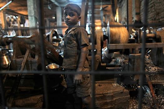 Rustam (10 tuổi), một công nhân nhícủa nhà máy nhôm ở Dhaka, Bangladesh, phải làm việc 12 tiếng mỗi ngày cùng 25 người bạn đồng trang lứa.