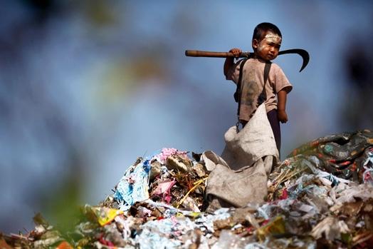 Cậu bé này là một người nhập cư bất hợp pháp, đang đi nhặt rác tại một bãi rác khổng lồ ở Mae Sot, Thái Lan.