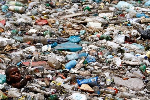 Paulo Henrique Felix da Silveira (9 tuổi) bơi trong biển rác ở khu ổ chuột Saramandaia, Recife, Brazil. Đối tượng hành nghề nhặt rác đông đảo ở đây đều có độ tuổi từ 10-17.