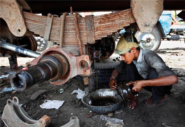 Cậu bé này tuy còn rất nhỏ tuổi nhưng đã phải làm việc trong một tiệm sửa ô tô ở New Delhi, Ấn Độ.