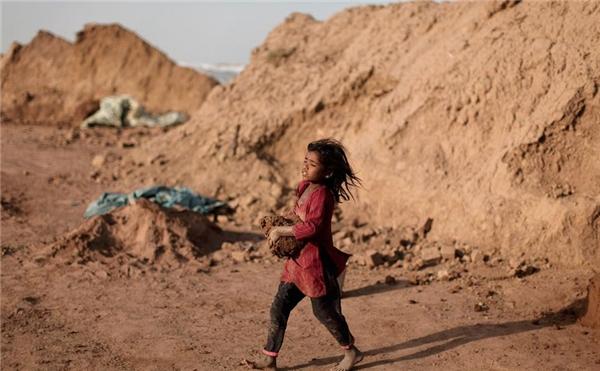 Naginah Sadiq (5 tuổi), công nhân của một xưởng đúc gạch ở Islamabad, Pakistan, đang đi nhặt đất sét về xưởng.