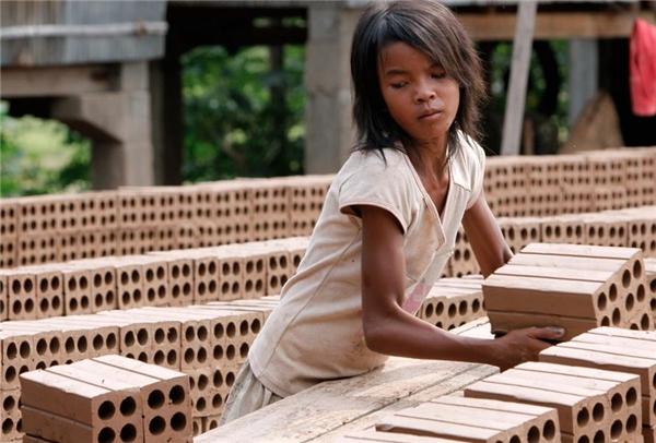Cô bé này phải còng lưng xếp từng viên gạch để phơi nắng lại một lò đúc gạch ở Chheuteal, Kandal, Campuchia.