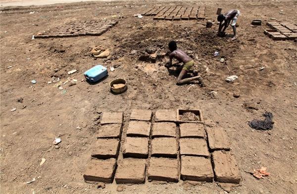 Giống như nhiều đứa trẻ khác ở Darfur, Takenin Khartoum, Sudan, hai cậu bé này kiếm tiền bằng cách đúc những viên gạch bằng bùn đất.
