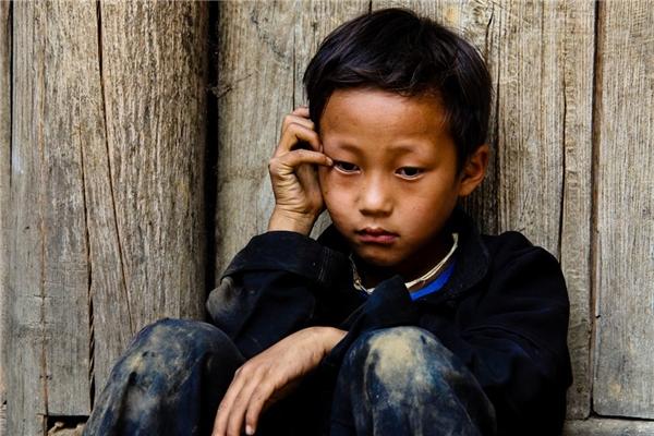 Một bé trai người Mông ở Sủng Là, Hà Giang, bị gia đình bắt phải chụp hình với khách du lịch nhưng em không thích và ngồi buồn bên hiên nhà. Từ khi du lịch phát triển, Sủng Là nườm nượp khách ghé thăm. Một số em nhỏ bị gia đình bắt phải đi theo du khách để xin tiền hoặc đòi tiền chụp ảnh cùng. (Ảnh: Internet)