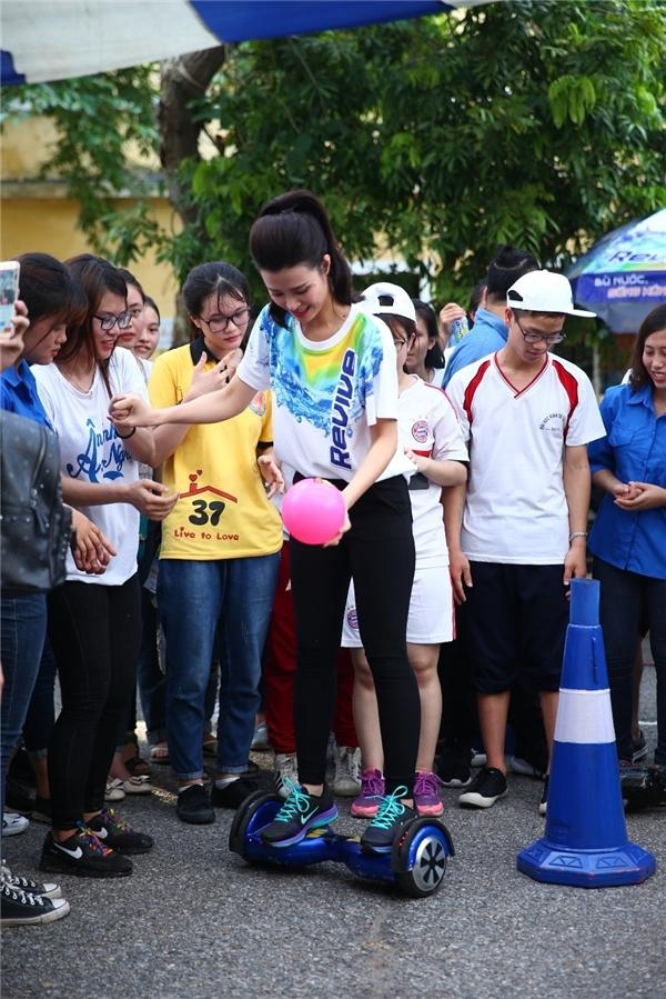 Nữ ca sĩĐông Nhi làm mẫu đi ván điện hoverboard với sự trợ giúp từ các fan.