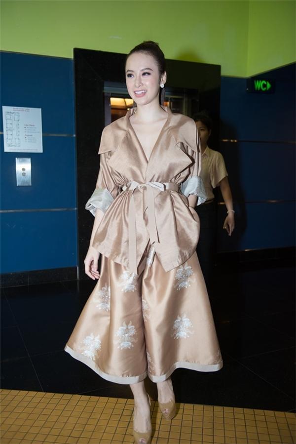"""Angela Phương Trinh cũng khiến khán giả, người hâm mộ bất ngờ khi diện bộ trang phục với sắc vàng đồng cùng chất liệu vải trơn, bóng khiến cô trở nên """"dừ"""" hơn."""