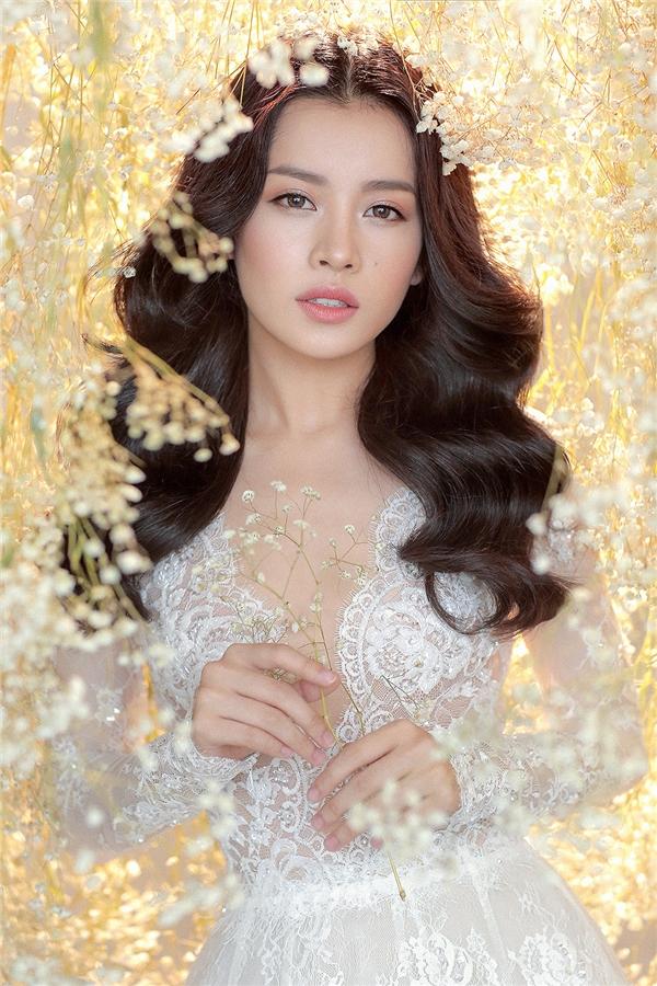 Giữa không gian tràn ngập hoa lá, ánh sáng, Chi Pu xuất hiện lộng lẫy như thiên thần trong bộ váy cưới trắng tinh trên nền chất liệu ren đối xứng gợi cảm, hợp xu hướng.