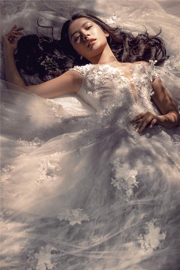 Trong không gian hòa hợp giữa hai mảng sáng tối, chiếc váy cưới trắng lại như màn sương mỏng kì ảo, huyền diệu, nhẹ tênh nhưng vẫn đủ lưu luyến, vương vấn người xem.