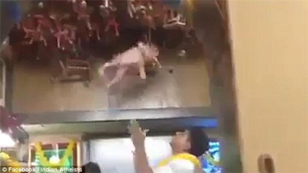 """""""Pháp sư"""" tung bé sơ sinh lên cao trước sự hào hứng của đám đông. (Ảnh cắt từ clip)"""