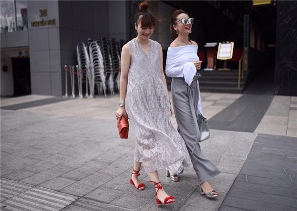 Hai chị em Yến Trang, Yến Nhi nổi bật trên phố với trang phục có màu trung tính: trắng, xám. Phụ kiện ánh bạc hay màu đỏ nổi bật được sử dụng làm điểm nhấn cho trang phục đơn giản, thanh lịch, ngọt ngào.