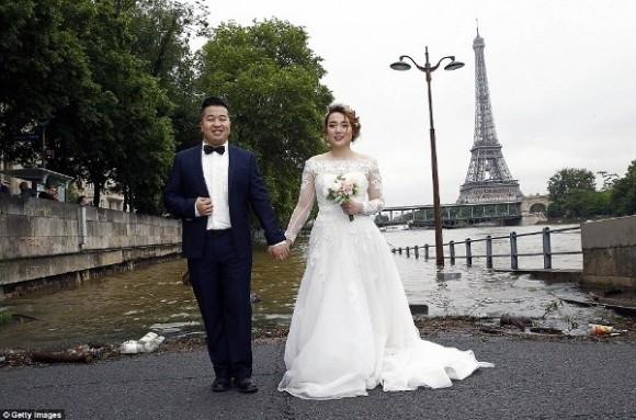 Cặp uyên ương này vẫn sẵn sàng chụp ảnh cưới bên bờ sông Seine, mặc dù nước đã dâng lên ngang với mặt đường.