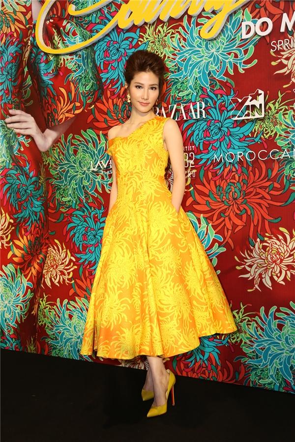 Diễm My 9X điệu đà, gợi cảm với váy lệch vai nền cam hoa vàng.