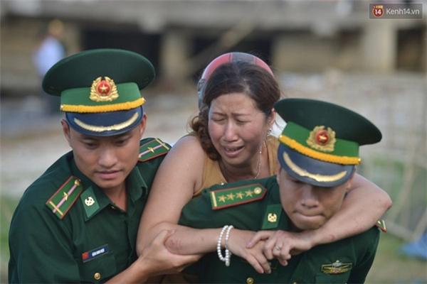 Người vợ đau đớn và khóc ngất khi phát hiện thi thể vừa được vớt lên là chồng mình - (Ảnh: Phương Thảo)