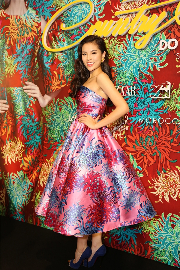 Hoa hậu Kỳ Duyên tươi cười rạng rỡ trên thảm đỏ. Cô diện thiết kế bồng xòe với nền hồng, hoa cúc xanh. Kỳ Duyên cũng là một trong những mĩ nhân có mặt sớm tại thảm đỏ lần này.