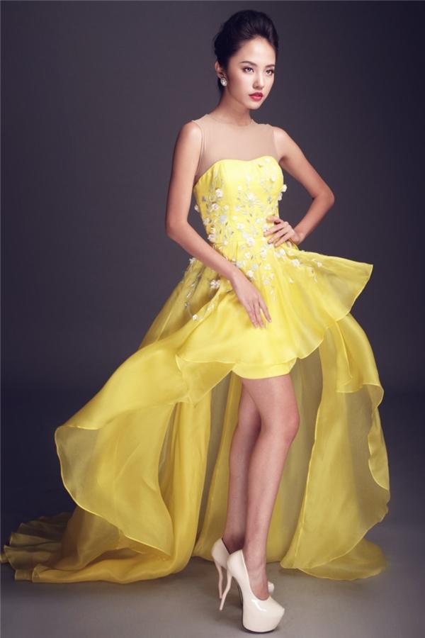 """Thanh Vy trẻ trung với sắc vàng và """"ăn gian"""" được chiều cao nhờ phom váy bất đối xứng. Thiết kế tạo điểm nhấn bằng họa tiết thêu tay truyền thống."""