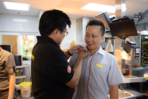 Ông Bảo Hoàng trao tặng huy hiệu cho anh Kenny, trưởng nhà hàng McDonald's Vincom Masteri.
