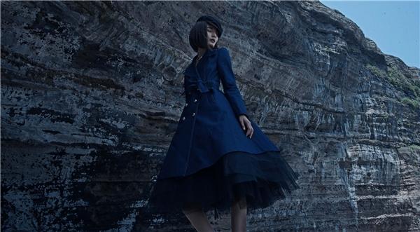 Nữ người mẫu hóa thân thành quý cô cổ điển trong dáng váy xòe kín đáo kết hợp lưới mỏng tang xếp tầng bên trong. Thiết kế được tạo điểm nhấn bằng đường cắt kết hợp chỉ vàng cam may nổi tạo hiệu ứng.