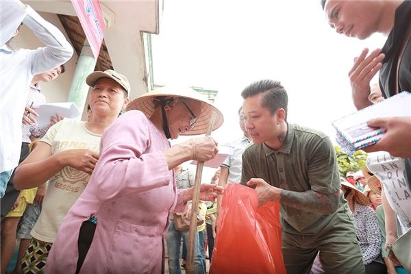 Nam ca sĩ tận tay trao từng phần quà tới cho người dân tại đây.