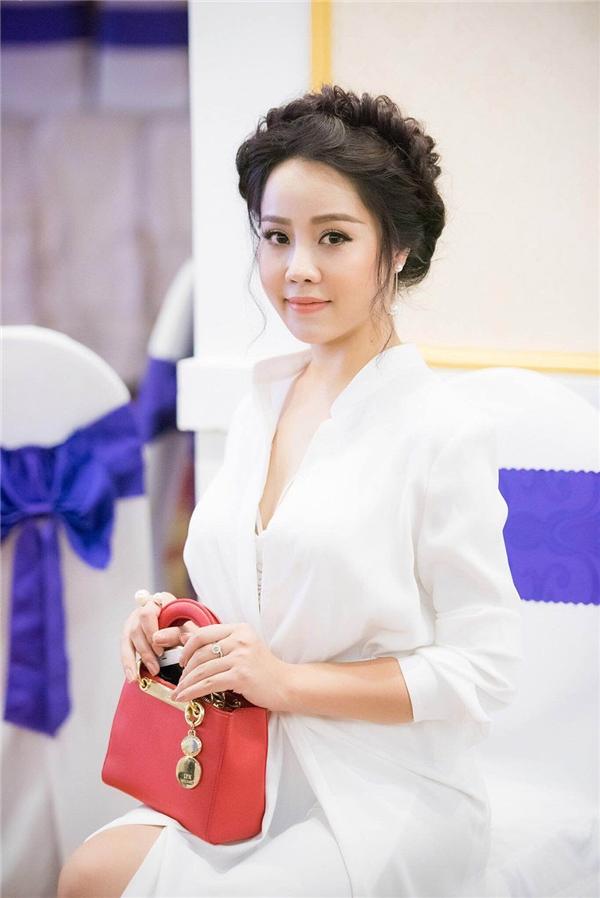 Cô kết hợp trang phục cùng túi cầm tay màu đỏ nổi bật.