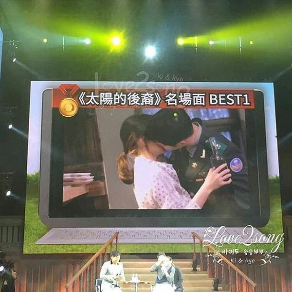 """Một số hình ảnh trong hậu trường phim """"Hậu duệ của mặt trời"""" được hé lộ trên màn hình lớn. Trong đó có cảnh SongJoong Ki trao nụ hôn """"rượu"""" cho Song Hye Kyo."""