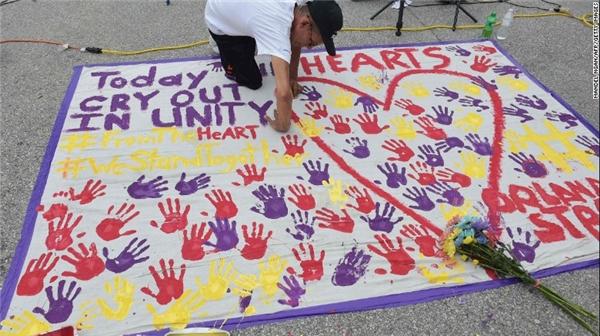 Một người đàn ông in dấu tay như một cách tưởng niệm các nạn nhân. (Ảnh: CNN)