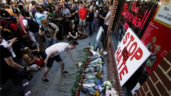 Từng dòng người đến khu vực tưởng niệm ngay trước Stonewall Inn, lặng lẽ đặt những cành hoa như một lời chia buồn. Stonewall được coi là cái nôi của các phong trào dành cho người đồng tính ở Orlando. (Ảnh: CNN)