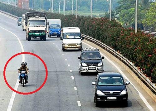 Người đi xe máy trong ảnh đã đè lên vạch liền để chạy vào làn ôtô. (Ảnh: Internet)