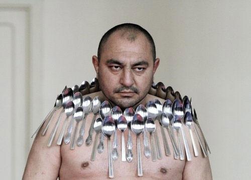 """Mọi người gọi người đàn ông trong ảnh là """"người nam châm"""" bởi anh đã xác lập kỉ lục hút nhiều thìa kim loại lên người nhất. Năm 2011, anh Etibar Elchiyev, người Gruzia đã hút được 50 chiếc thìa lên người. (Ảnh: Internet)"""