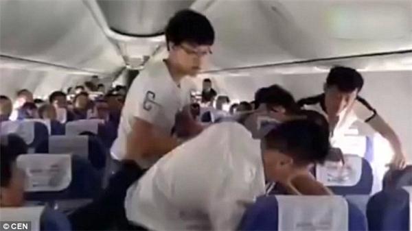 Một vài hành khách giúp đỡ các tiếp viên hàng không khống chế vị khách gây rối này trong khi mọi người xung quanh chỉ theo dõi. (Ảnh: CEN)