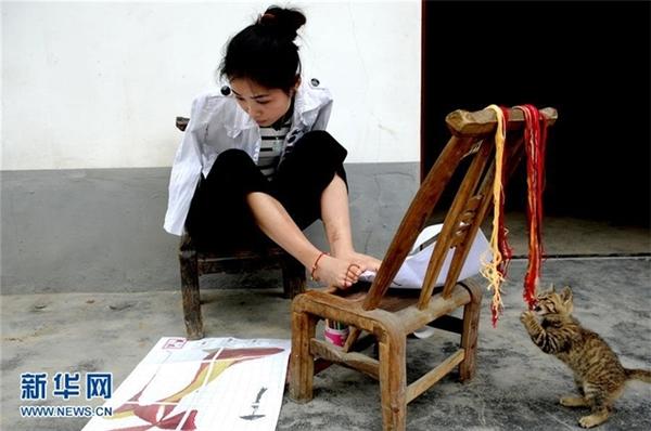 Chỉ với đôi chân này, Yang đã tạo nên những bức tranh thêu tuyệt đẹp.(Ảnh: News.cn)