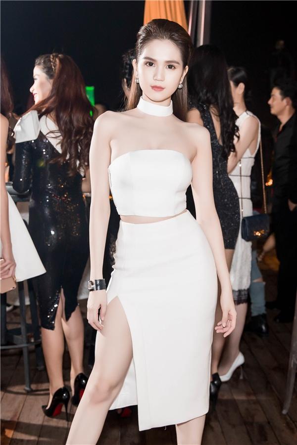 Tham gia đêm tiệc tối qua, Ngọc Trinh diện cây trắng kết hợp giữa crop-top cùng chân váy xẻ tà. Vòng cổ chocker đi kèm giúp bộ trang phục trở nên cá tính, ấn tượng hơn.