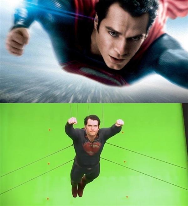 Superman được treo bằng hệ thống dây cáp, lơ lửng phía trước phông nền xanh.