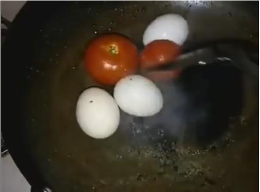 """Cô gái xào cà chua với trứng """"nguyên con""""... (Ảnh: Cắt clip)"""