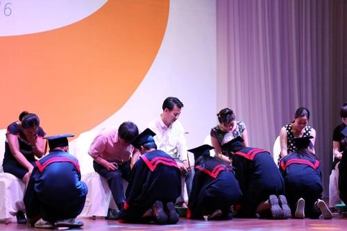 Các em học sinhquỳ gối tự tay rửa chân cho cha mẹ.