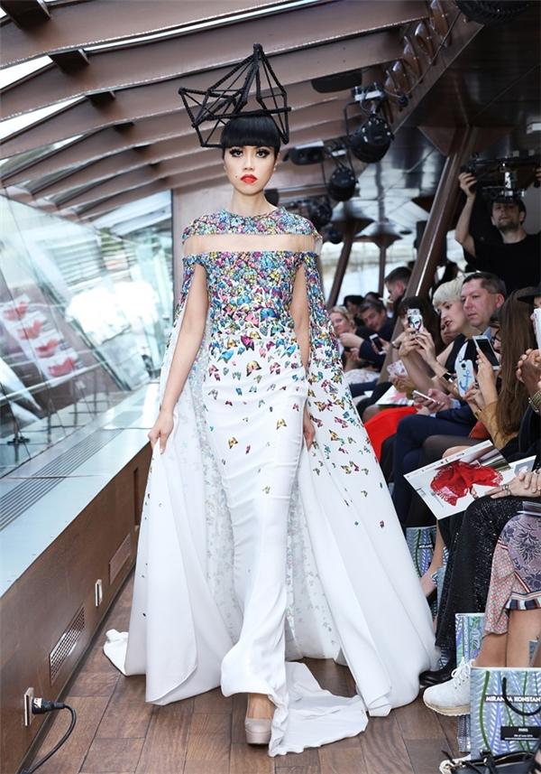 Chốt màn show diễn, nữ người mẫu diện bộ váy tay cape hợp xu hướng kết hợp họa tiết hoa bướm với nhiều tông màu nổi bật.
