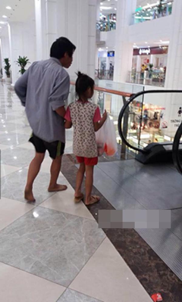 """Hai cha con """"lạ đời"""" như lạc lõng giữa trung tâm mua sắm sang trọng. (Ảnh: Beatvn)"""