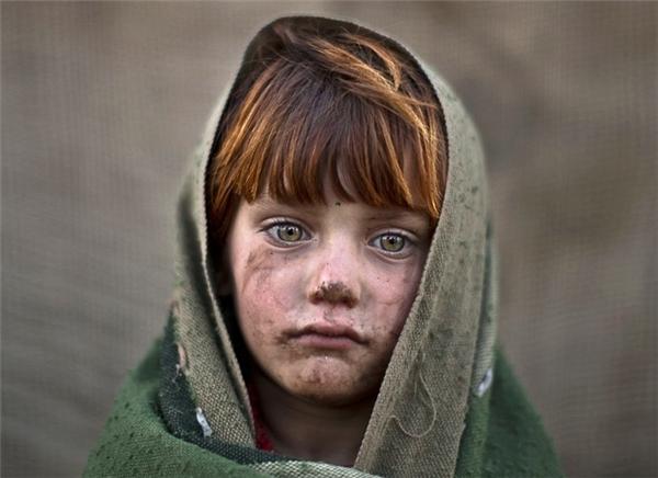 Laiba Hazrat, bé gái 6 tuổi người Afghanistan, trùm chăn trong giá lạnh ở ngoại ô Islamabad, Pakistan. (Ảnh: AP)