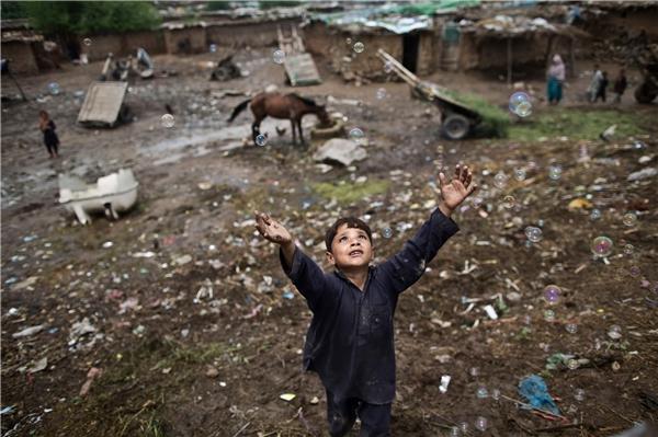 Zawar Khan, một trẻ tị nạn người Afghanistan khác, đuổi theo những quả bong bóng xà phòng mà những đứa trẻ khác thổi ra trong một sân chơi ở khu tị nạn ngoại ô thủ đô Pakistan. Không biết liệu rồi tương lai của em có mong manh như những quả bong bóng xà phòng này hay không? (Ảnh: AP)