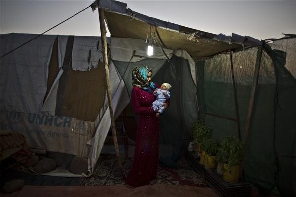 Trong khi những đứa trẻ khác được chăm sóc bởi các đội ngũ y tế hiện đại, thì con của cô Huda Alsayil, 20 tuổi lại bị sinh ra trong một trại tị nạn ở Mafraq với điều kiện vật chất thiếu thốn. (Ảnh: AP)