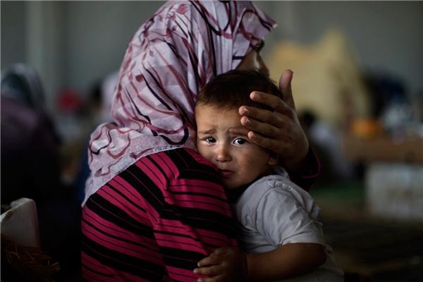 Ánh mắt ám ảnh của bé Amjad Al-Saleh, cùng mẹ bên ngoài khu tị nạn ở biên giới Syria – Thổ Nhĩ Kỳ. Họ hivọng tới được các trại tị nạn ở quốc gia láng giềng. (Ảnh: AP)